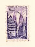 An old french postage stamp with an image of a church and old houses stock photo