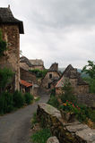 Old french village. Street view of the medieval french village la Vinzelle in the Cantal, with beautiful romantic houses and flowers, on an overcast day Royalty Free Stock Photography