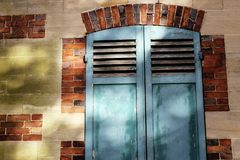 Closed shutters old french windows. Old french window with blue closed wooden shutters in brick wall, with last rays of sunshine and signs of humidity on the royalty free stock images