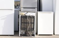 Old fridges freezers refrigerant gas at refuse dump skip recycle stacked pile plant help environment reduce pollution white silver stock image