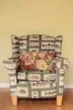 An Old Friend. A tacky Arm Chair with a fish pattern well worn and broken in Royalty Free Stock Photography