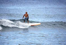 Old Friend Surfing. Older gentleman riding waves in the pacific ocean royalty free stock photo