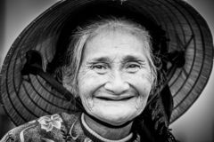 Old friendly woman with vietnamese straw hat stock image