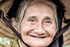 Old friendly woman with vietnamese straw hat royalty free stock images