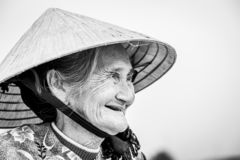 Old friendly woman with vietnamese straw hat royalty free stock image