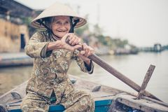 Old friendly woman with vietnamese straw hat royalty free stock photo