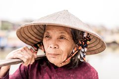 Old friendly woman with vietnamese straw hat stock photography