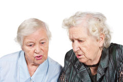 Old friends. Two old women sitting together; isolated on white Stock Photography
