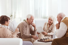 Old friends competing over chess. Two old friends competing over a game of chess Stock Photo