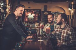 Old friends drinking draft beer at bar counter in pub. Stock Image