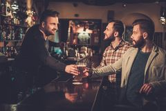 Old friends drinking draft beer at bar counter in pub. Royalty Free Stock Images