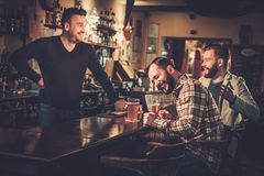 Old friends drinking draft beer at bar counter in pub. Stock Images