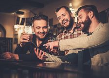 Old friends having fun with smartphone and drinking draft beer at bar counter in pub. Cheerful old friends having fun with smartphone and drinking draft beer at Royalty Free Stock Image