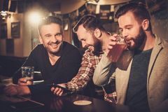 Old friends having fun with smartphone and drinking draft beer at bar counter in pub. Stock Images