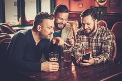 Old friends having fun with smartphone and drinking draft beer in pub. Cheerful old friends having fun with smartphone and drinking draft beer in pub Stock Image