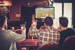Old friends having fun watching a football game on TV and drinking draft beer at bar counter in pub. Royalty Free Stock Photography