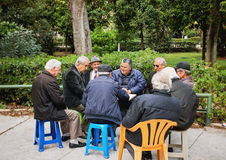 Old friends playing cards and laughing in National Garden park Royalty Free Stock Photos