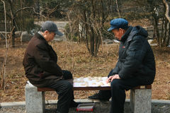 Old friends playing a game. Chinese men playing mahjong Stock Photo