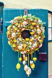 Old front door ornamented with colorful easter wreath royalty free stock images
