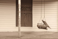 Old Front Porch with Swing. An old swing on the front porch of an abandoned house Royalty Free Stock Photos