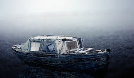 Old frozen boat. Photomontage with an old decayed boat on a frozen background Stock Photos