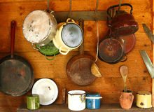 Old frying pans and cooking pots hanging on a wooden wall Stock Image