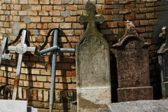 Old funeral stones and metal crosses supported by the wall of a church in the cemetery. royalty free stock photography