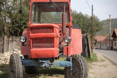 Old funny traktor. Old red funny traktor in the village Royalty Free Stock Image