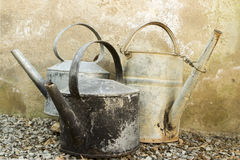 Old galvanised kettles and watering can. Old lidless galvanised kettles and a watering can standing on gravel in a group with their long spouts pointing outwards Royalty Free Stock Images
