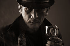 Old gangster and a glass of wine Stock Images