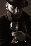 Old gangster with sinister eye. Portrait of old gang lord with sinister eye holding glass of wine Royalty Free Stock Photography