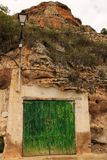 Old garage with green wooden door excavated in the mountain royalty free stock photo