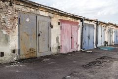 Old garages with multicolored iron gates. Garage cooperative. Rows of car garages. City architecture. Transport industry. Stone sheds. Rusty iron gate. Brick royalty free stock image