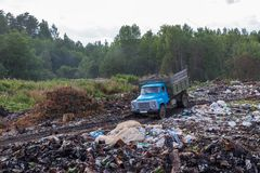 Old garbage truck rides on illegal garbage dump in the woods royalty free stock images