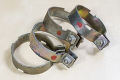 Old garden accessories. Rusty hose clamps on the workshop table. Light background stock photos