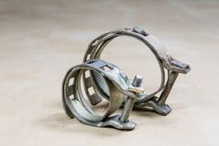 Old garden accessories. Rusty hose clamps on the workshop table. Light background royalty free stock image