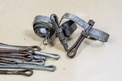 Old garden accessories. Rusty hose clamps on the workshop table. Light background royalty free stock photo