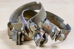 Old garden accessories. Rusty hose clamps on the workshop table. Light background stock photo