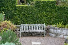 Old Garden Bench. An old wooden garden bench in a formal garden royalty free stock images