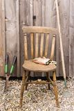 Old Garden Chair and Tools. An old fashioned wooden chair with work gloves and garden tools leaning against a timber shed in the background ideal for retirement stock photos
