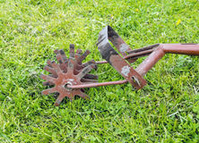 Old garden cultivator on green grass Royalty Free Stock Photo