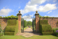 Old garden gates with topiary shrubs stock images
