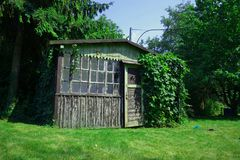 Old garden house. Old uncared-for ivied garden house surrounded by green nature but with connection to electricity Stock Image