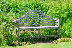 Old garden seat. Beautifully designed old garden seat in pride of place in the summer sun, framed against the greenery of an English country garden Stock Images