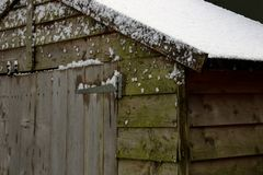 Old garden shed with snow on roof Stock Image