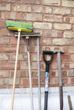 Old garden tools. Green broom and old garden tools against a wall royalty free stock photography