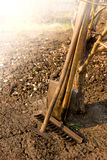 Old garden tools. Old retro garden tools (cultivator, shovel, rake) over brown soil (ploughed land) close up, vertical.  Agriculture, gardening, soil cultivation Stock Photos