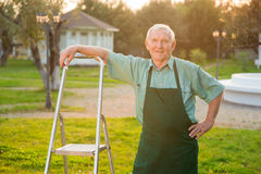 Old gardener smiling. Man with stepladder outdoors Stock Image
