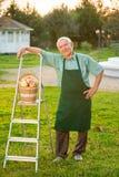 Old gardener standing on grass. Stock Photo