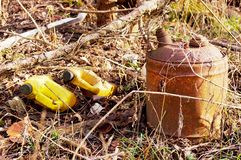Old gas can and garbage. Old gas can and garbage in overgrown vegetation royalty free stock photo